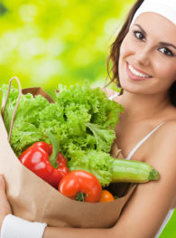 Portrait of happy smiling young beautiful woman in fitness wear holding grocery shopping bag with healthy vegetarian food, outdoors